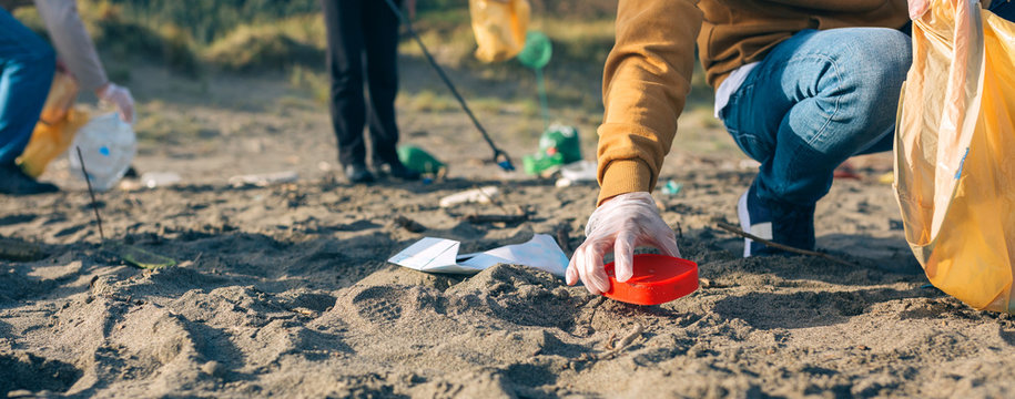 Unrecognizable young man picking up trash with group of volunteers on the beach