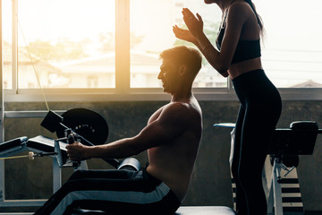 Young Caucasian man in white shirt at a gym, training hard and pulling weights in seated cable row machine with support from female fitness personal trainer. Sport fitness and muscles concept