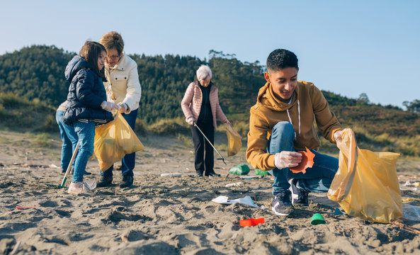 Young man picking up trash with group of volunteers on the beach
