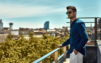Handsome man in summer time looking on city view Wall mural