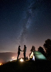 Silhouette of happy romantic couple tourists standing at campfire near tourist tent, holding hands under night sky full of stars and Milky way. On background starry sky, mountains and luminous city