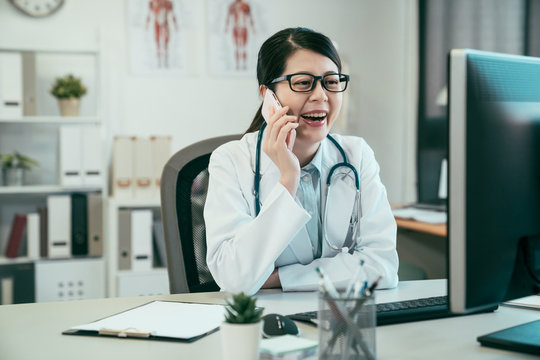 asian woman doctor having phone call in medical office. young japanese girl nurse in white coat laughing cheerful chatting on smart phone. smiling female staff in hospital clinic enjoy break time.
