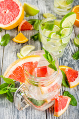 Summer refreshment drinks. Four types of citrus lemonade or mojito cocktail - orange, lime, lemon, pink grapefruit. Infused citrus water. On a wooden white background,