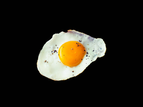 Fried egg sunny side up with pepper isolated on black background