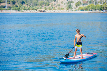 Paddle boarder. Child boy paddling on stand up paddleboard. Healthy lifestyle. Water sport, SUP surfing tour