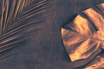 Closeup of bronze palm and monstera leaves on abstract dark purple textured background. Tropical conceptual elegant trendy toned summer background. Flat lay. Copy space. Wall mural