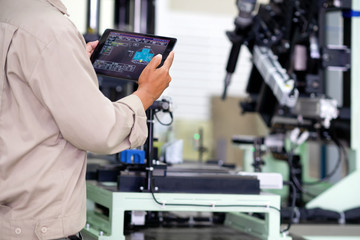 Engineer using digital tablet for testing operation of machine in  manufacturing factory plant.