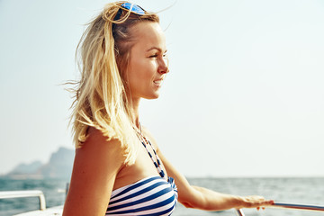 Smiling young woman taking in the ocean view from a boat