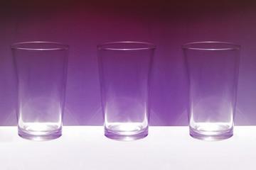 Tres basos de cristal sobre fondo purpura iluminado
