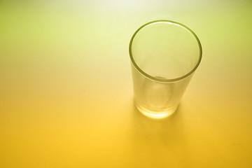 Un baso de cristal sobre fondo iluminado amarillo