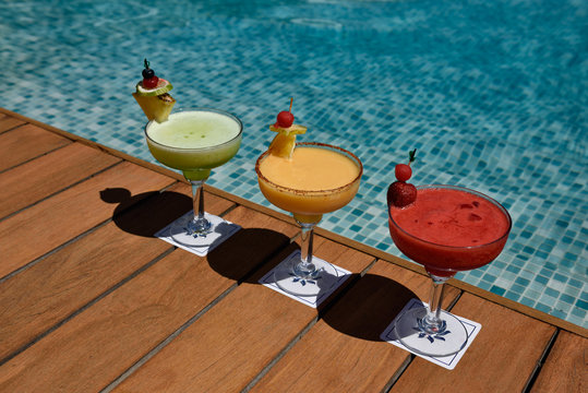 Three colorful alcoholic drinks on a deck next to a pool
