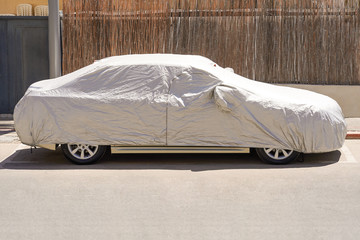 A car parked with protective cover silver. Car under a protective cover parked in the courtyard in sun weather, summer. Car with a protective, parking cover. The car is covered with a cover Wall mural