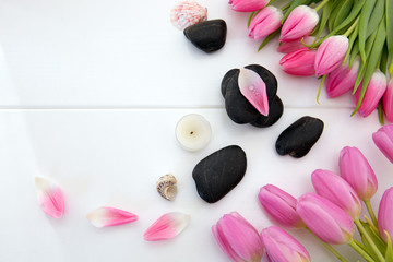 Foto auf Acrylglas Tulpen Spa setting with tulips , black stones and candle on white wood background.