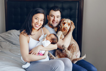 Smiling Chinese Asian mother and Caucasian father with mixed race newborn infant baby son daughter and large pet dog. Happy family in bedroom. Home lifestyle authentic natural moment.