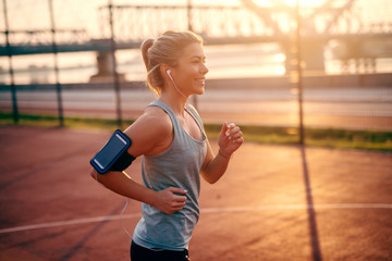 Charming female blonde runner in sportswear running on court with earphones in ears and smart phone in phone case around arm. No matter how slow I run, I'm still faster than my couch.