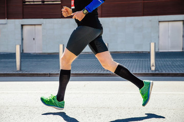 Fototapete - legs man runner athlete in compression socks running marathon
