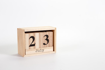 Wooden calendar July 23 on a white background