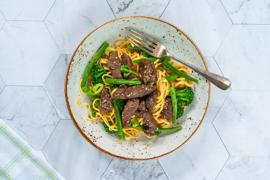 Honey and sesame beef noodles with green vegetables - top view