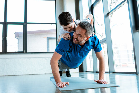 happy father doing push up exercise with son on back at gym with copy space