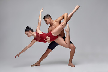 The couple of an athletic modern ballet dancers are posing against a gray studio background.