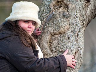 A young woman with gray eyes, a white hat and warm clothes embracing a tree trunk