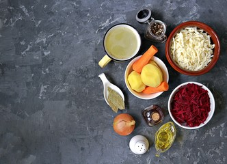 Ingredients for cooking borscht, traditional hot Russian soup with beetroot, cabbage and potatoes on a dark gray concrete background.