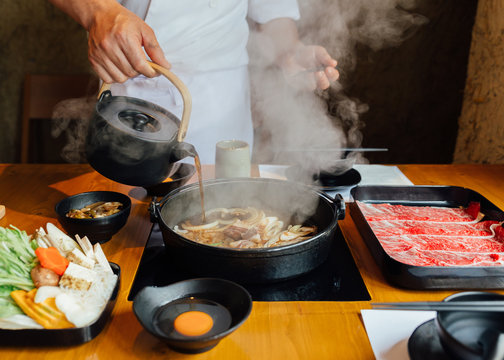 Chef is pouring soy sauce on stir fried vegetables such as onion, cabbage, scallion and tofu and more in hot pot with steam before boiling Wagyu beef.