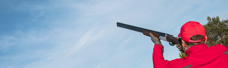 man shooting trap or skeet with a shotgun,  clay pigeon shooting on the sky background, panoramic banner , Images with Copy Space