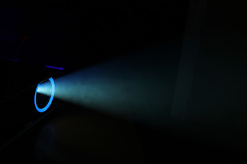Blue rays of light through the smoke from the projector. Lighting equipment. Show, performance, concert or night club. Abstract Background
