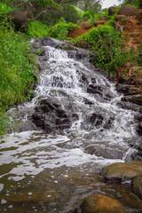 Waterfall and red dirt along the hiking trail to Queen's Bath, Kauai, Hawaii, USA