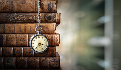 Vintage clock hanging on a chain on the background of old books. Old watch as a symbol of passing time. Concept on the theme of history, nostalgia, old age. Retro style. Wall mural