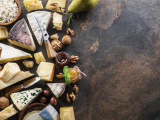 Wall Mural - Cheese platter with organic cheeses, fruits, olives and jam on stone background. Tasty cheese starter.
