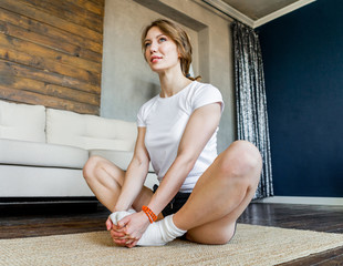 Young blonde woman doing stretching yoga exercises at home. Healthy lifestyle.