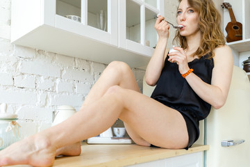 Woman eating yogurt in white bright apartments. Diet keeping and Loosing weight.