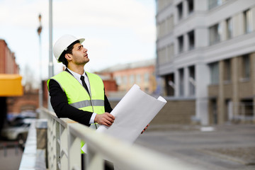 Portrait of Mixed Race engineer holding plans standing at construction site outdoors, copy space