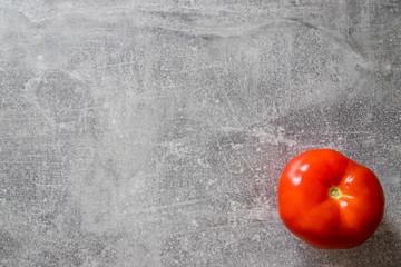 Obraz Pomidor czerwony, malinowy na betonie - fototapety do salonu