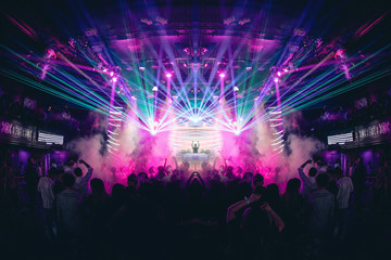 DJ with Hands up in a Nightclub with Lasers