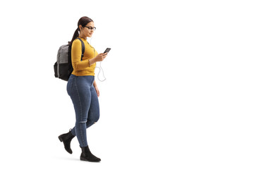 Female student walking and choosing a song from her mobile phone Wall mural