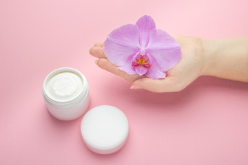 Cadres-photo bureau Spa Mockup for hand or face skin care natural cosmetics. Jar of face cream, orchid flower in hand on a pink background. Natural organic cosmetics with herbal extract. Beauty or cosmetology concept.