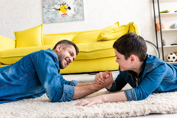 father and son lying on carpet and arm wrestling at home