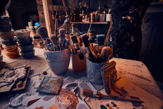 There are dark and a lot of different brushes on artist's table in jars. There are artistick's mess on the table.