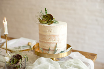 Elegant white wedding cake with flowers and succulents in boho style. Rustic Wedding Cake