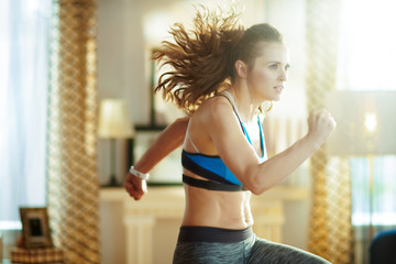 healthy woman in fitness clothes in modern house workout