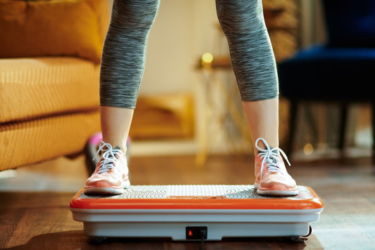 Closeup on young woman training using vibration power plate