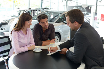 Verkaufsgespräch im Autohaus // young couple buying a new car in the showroom of a car dealership - signature sales contract with seller