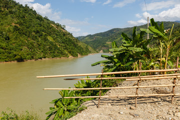 Nam na River, Vietnam mountain river and bamboo fence in the foreground