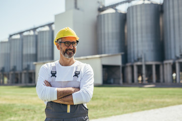 middle aged agricultural worker standing crossed arms in front of grain silo Fotomurales