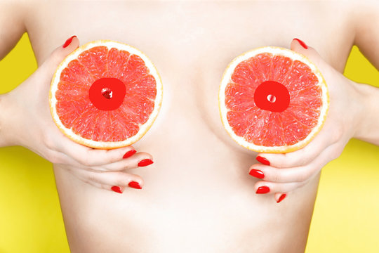 Sexy young woman holding grapefruits near her breasts on color background. Erotic concept