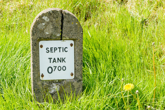Concrete post marking the location of a septic tank