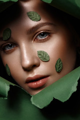 Beautiful fresh girl with perfect skin, natural make up and green leaves. Beauty face. Close up